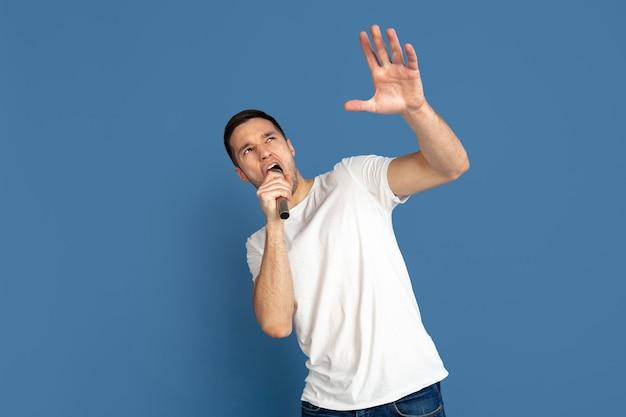 有名人、星のように歌います。青いスタジオの壁に白人の若い男の肖像画。