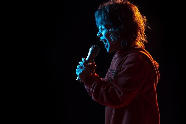 Пою как знаменитость, рок-звезда. портрет кавказского мальчика на темном фоне студии в неоновом свете. красивая фигурная модель.