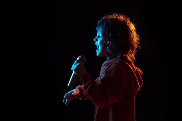 유명인처럼 노래 해요, 록 스타. 네온 불빛에 어두운 스튜디오 배경에 백인 소년의 초상화. 아름다운 곱슬 모델.