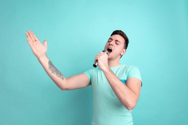 Cantare come una star. ritratto del giovane caucasico isolato sulla parete blu dello studio