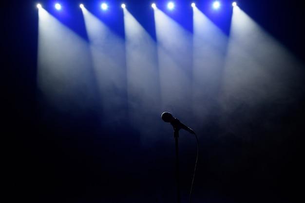 歌手の準備ができて歌うマイク。マイクと舞台照明。歌とカラオケ。