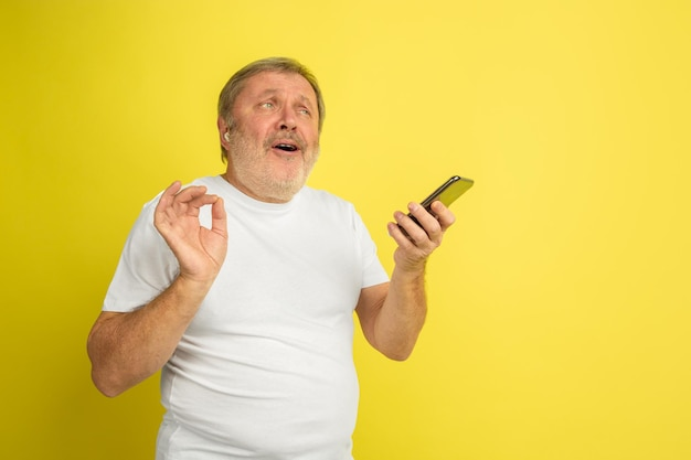 イヤホンとスマートフォンで歌います。黄色のスタジオの背景に白人男性の肖像画。白いシャツの美しい男性モデル。