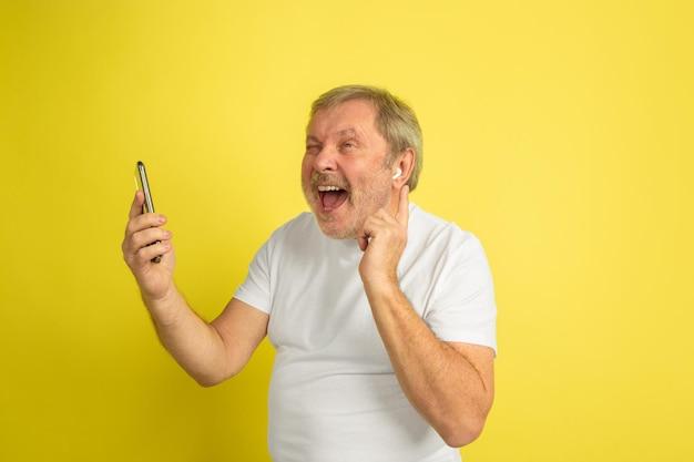 Cantando con auricolare e smartphone. ritratto di uomo caucasico su sfondo giallo studio. bellissimo modello maschile in camicia bianca.