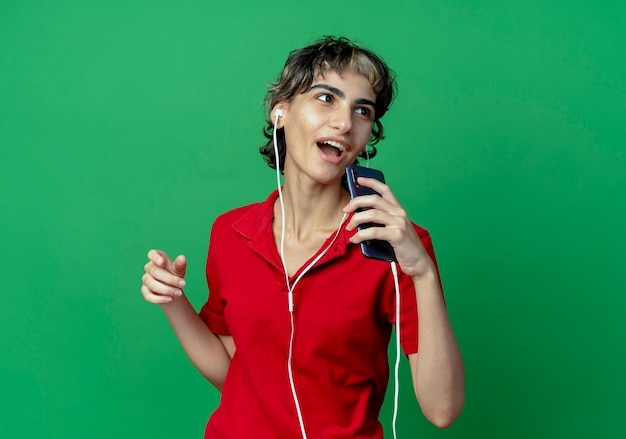 Поющая молодая кавказская девушка с прической пикси в наушниках и с помощью мобильного телефона в качестве микрофона, глядя в сторону