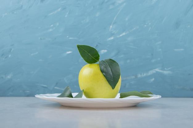 Одно яблоко с листьями на белой тарелке.