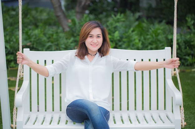 단일 아시아 여성 성인 공원에서 그네 벤치에 앉아 휴식을 취하십시오. 건강한 삶의 개념을 즐기십시오.