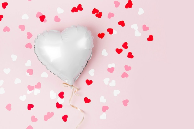 Одиночный воздушный шар из фольги в форме сердца на пастельно-розовом фоне. концепция любви. праздник. день святого валентина или украшение свадьбы / девичника. металлический шар