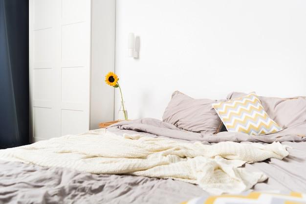 Single beautiful yellow sunflower in vase near bed in bedroom