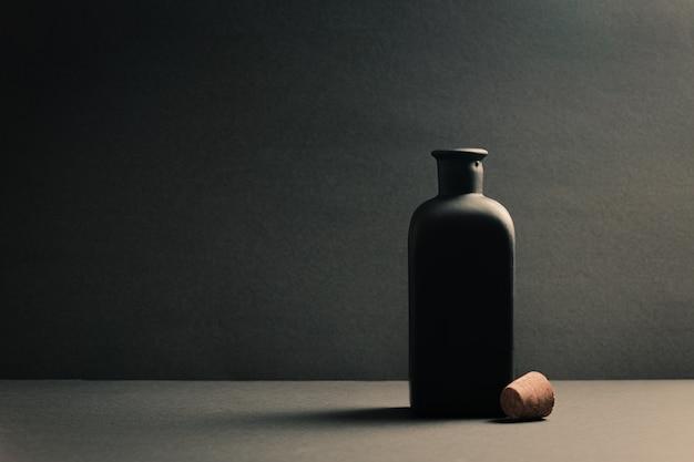 暗い背景の上にプラグをオフにした1つの黒いセラミックボトル