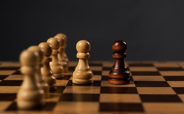 체스 보드에 흰색의 그룹에 대 한 단일 검은 폰