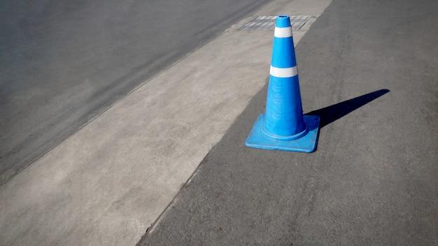 Single blue traffic road cone with white stripe