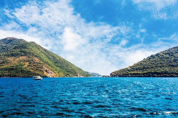 Single boat over the blue calm lake near the green mountain