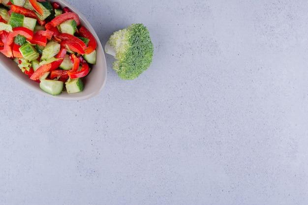 Singolo pezzo di broccoli accanto a una ciotola grigia di insalata mista su sfondo marmo. foto di alta qualità