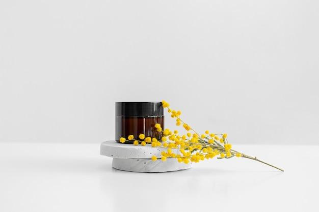 콘크리트 받침대와 노란색 미모사 꽃 회색 배경에 검은색 캡이 있는 단일 갈색 유리 항아리. 크림, 세럼, 로션. 제로 웨이스트 에코 글라스 용기. 유기농, 천연 화장품. 미용, 스킨케어