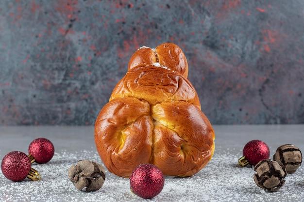 大理石のテーブルの上のクリスマスの装飾の輪の中で直立している単一のパン。