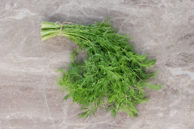 Single bundle of dill on marble.