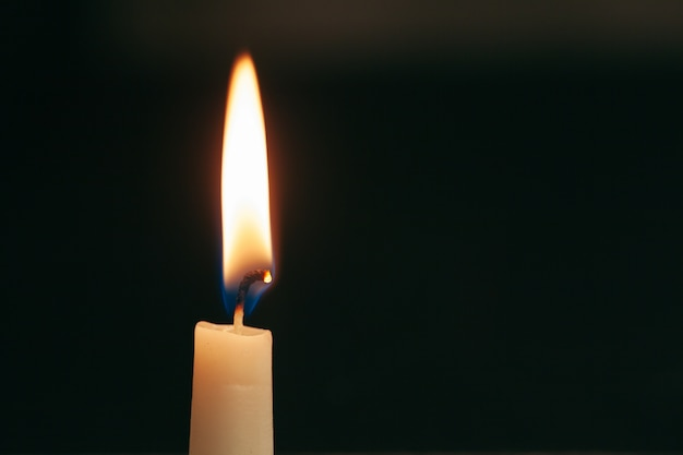 A single burning candle isolated with black background