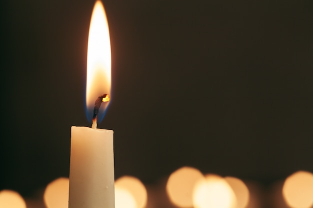 A single burning candle isolated with black