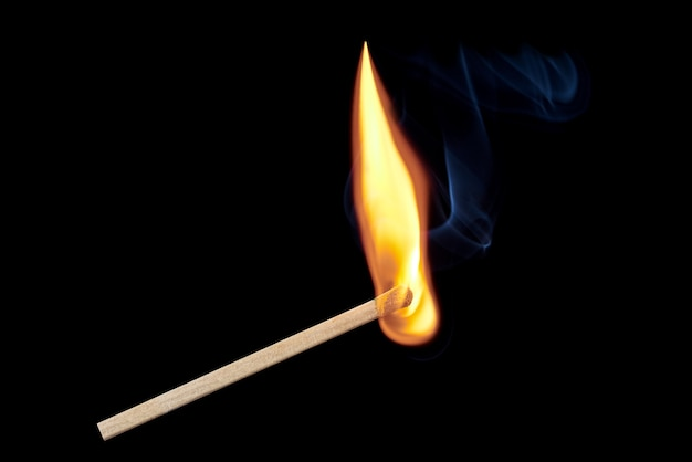 A single burning match with flames and smoke rising up isolated on a black background