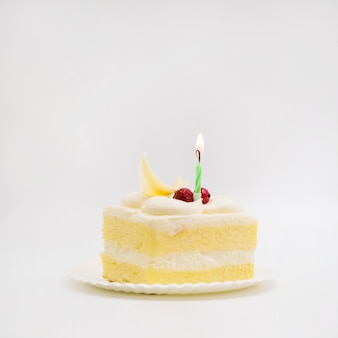 Single candle over the cake slice against white background