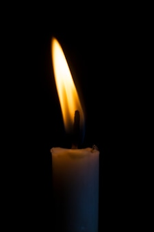Single candle in the dark