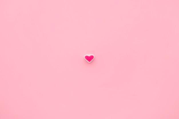 분홍색 배경에 단일 사탕 마음