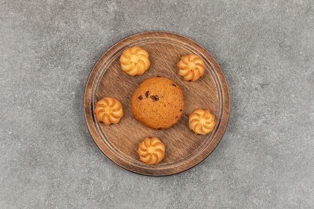 Singolo biscotto e biscotti al cioccolato sulla tavola di legno.