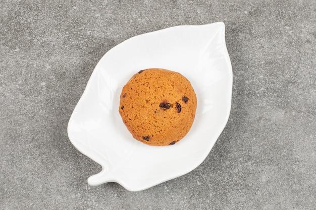 Одно шоколадное печенье на белой тарелке.