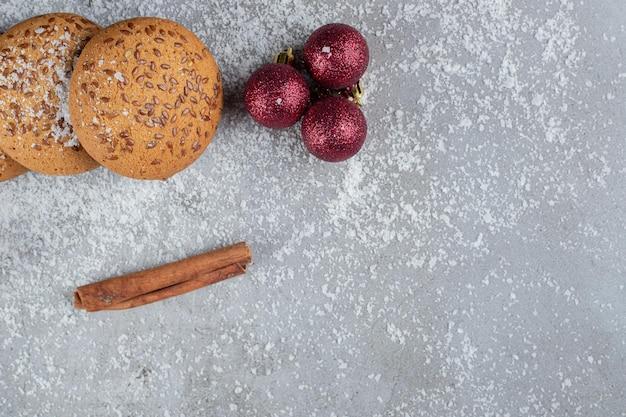 Single cinnamon stick, cookies, decorative balls and a branch on marble surface