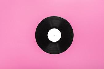 Single circular vinyl record on pink background