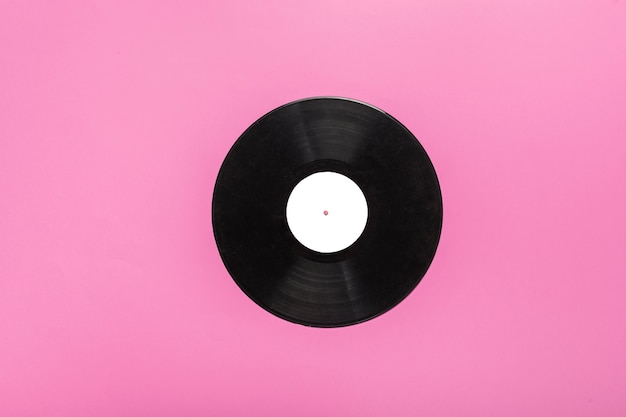 Single circular vinyl record on pink background