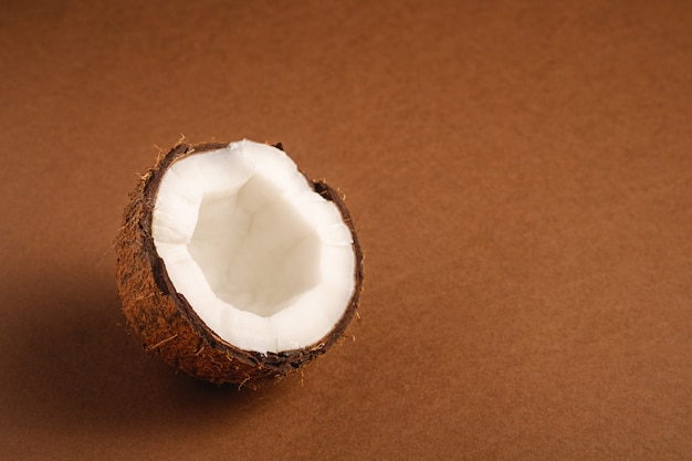 Single coconut fruit on brown plain surface, abstract food tropical concept, angle view copy space
