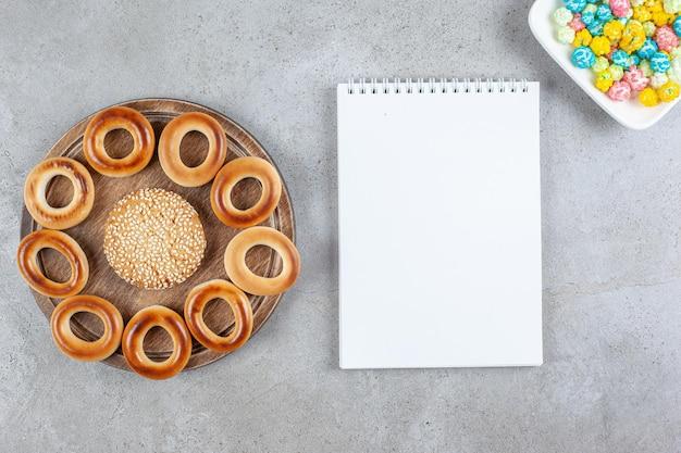 노트북 옆 나무 보드에 sushki와 대리석 배경에 팝콘 사탕 접시에 둘러싸인 단일 쿠키. 고품질 사진