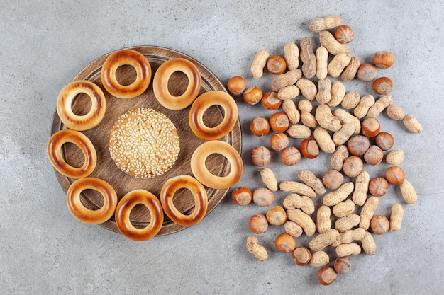 대리석 표면에 흩어져 있는 견과류 옆에 있는 나무 판자에 스시로 둘러싸인 단일 쿠키.