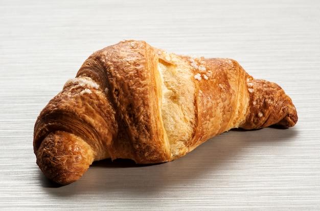 Single croissant on white table