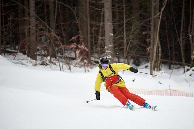 若い男性スキーヤーのダウンヒルスキーとカービングターンのシングルディセントは、高い樹木が茂った斜面をオンにします。降雪時のスキー