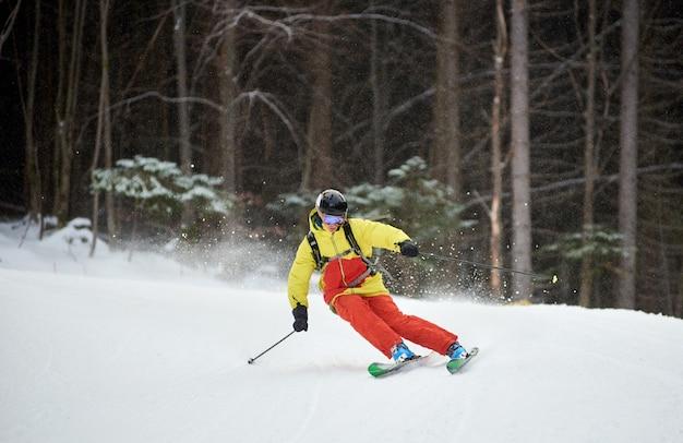 若い男性スキーヤーのダウンヒルスキーとカービングターンの単一の降下は、高い樹木が茂った斜面をオンにします。降雪時のスキー
