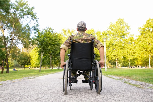 Single disabled retired military man in wheelchair moving down footpath in city park. back view. veteran of war or disability concept