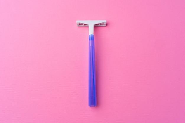 분홍색 배경 평면도에 단일 일회용 면도기, 복사 공간