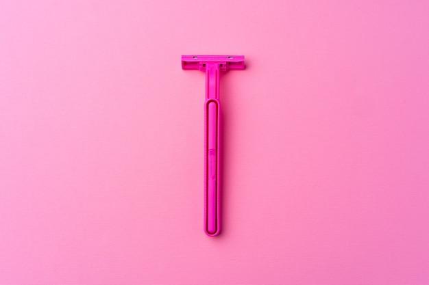 분홍색 배경 평면도에 단일 일회용 면도기