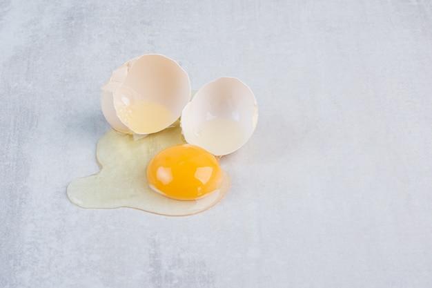 Unico uovo rotto aperto sul tavolo di marmo.