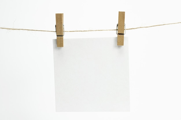 Single empty paper sheet for notes that hang on a rope with clothespins and isolated on white.