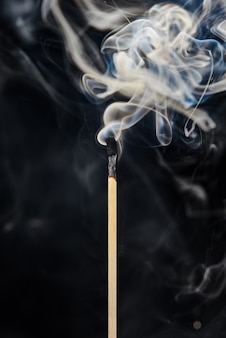 A single extinguished match with smoke rising up isolated on a black background