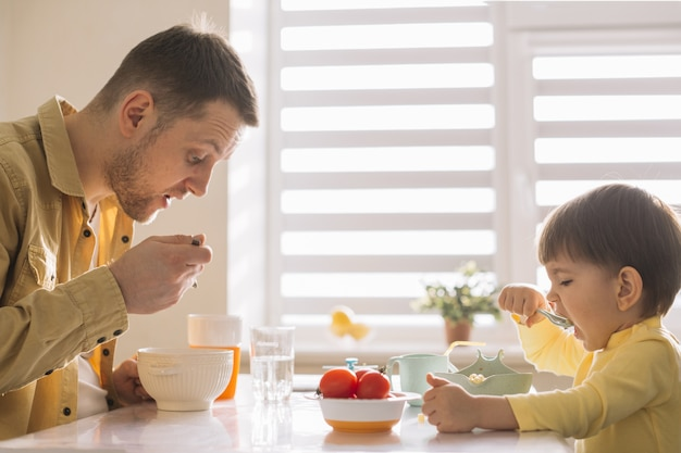 Single-father and child eating cereals