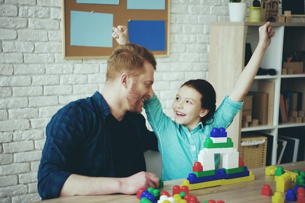 Single father with daughter are built tower.