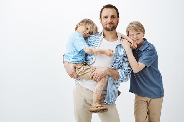 Отец-одиночка с двумя милыми детьми стоя. папа держит маленького сына на руках и широко улыбается, пока старший брат опирается на плечо