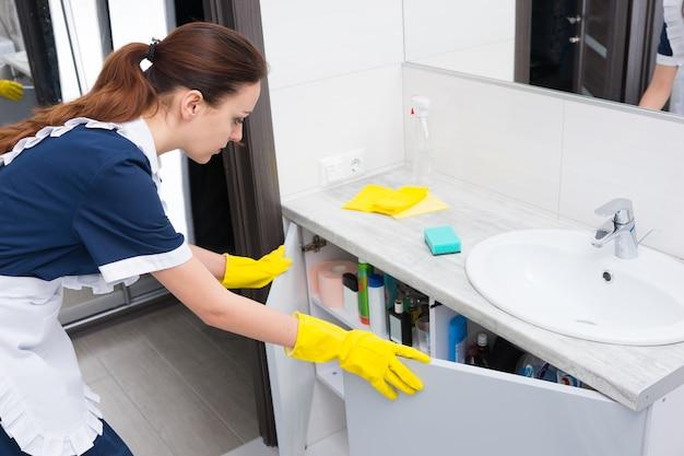 彼女の手に黄色の手袋と青いドレスと白いエプロンオープニングシンクキャビネットの独身女性家事労働者