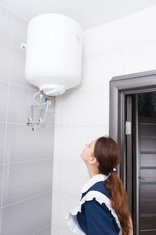 포니테일과 파란색과 흰색 유니폼을 입은 단일 여성 호텔 하녀가 욕실의 천장에 설치된 물 탱크를 검사합니다.