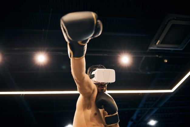 Single fighter in the ring wearing a virtual reality headset practicing straight blow