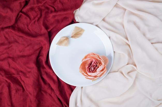 赤とピンクのテーブルクロスと白いプレート上の単一の花。